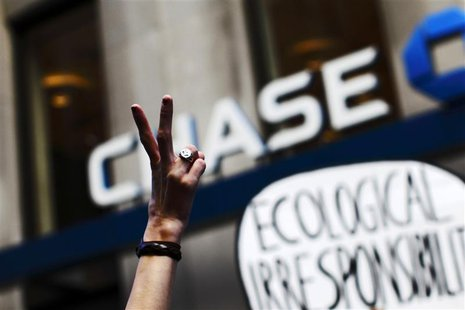 An Occupy Wall Street protestor flashes a peace sign during a march on Broadway past a Chase bank in New York's financial district September