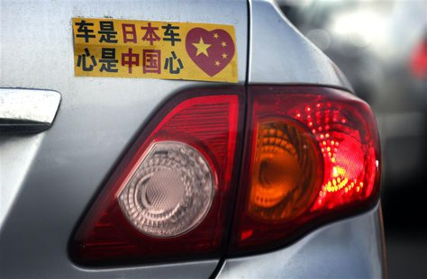 A Toyota car with a sticker attached to the rear can be seen along a main road in central Beijing in this October 16, 2012 file photo. REUTE