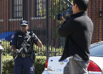 A U.S. Navy policeman (L) lifts his weapon as he warns a cameraman to move away from the main gate at the Washington Navy Yard, September 17
