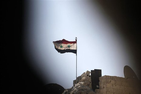 A Syrian national flag flutters over a building controlled by forces loyal to President Bashar Al-Assad in Ashrafieh, Aleppo September 17, 2