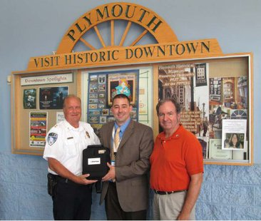 Plymouth Police Chief Jeff Tauscheck, Plymouth Walmart Manager Scott VanStraten, and Mayor Don Pohlman (left to right) posing with a new AED device for the Plymouth Police Department