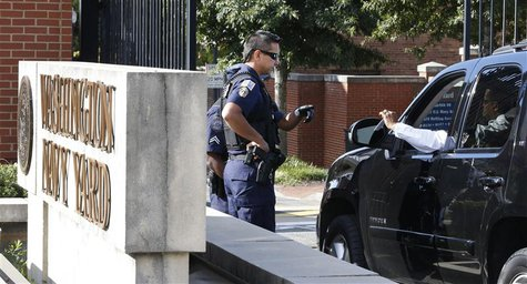 Police officers stop a vehicle to check identification at the main gate of the Washington Navy Yard in Washington, September 17, 2013. REUTE