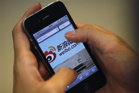 A man uses his phone to visit the Sina Weibo microblogging site in Shanghai, in this file picture taken May 29, 2012. REUTERS/Carlos Barria/