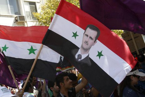 Supporters of Syria's President Bashar al-Assad wave a Syrian national flag depicting Assad's portrait during a rally in front of the parlia