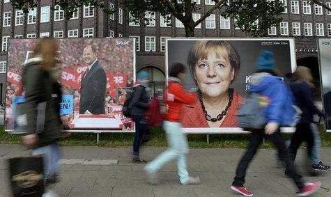 Teenagers pass election posters of Social Democratic top candidate Peer Steinbrueck (SPD) (L) and German Chancellor Angela Merkel (CDU) in H