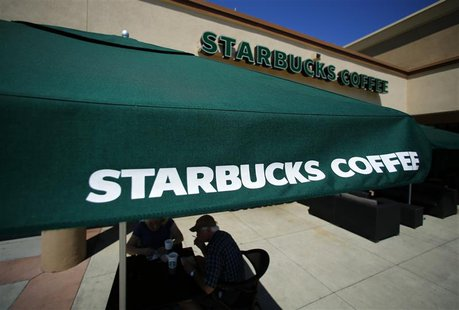 Customers enjoy their drinks outside a newly designed Starbucks coffee shop in Fountain Valley, California August 22, 2013. REUTERS/Mike Bla