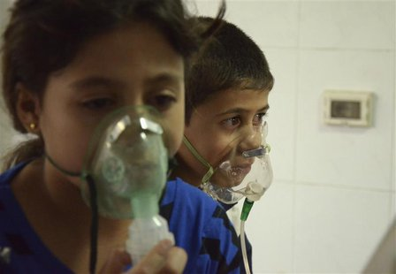 Children, affected by what activists say was a gas attack, breathe through oxygen masks in the Damascus suburb of Saqba, August 21, 2013. RE
