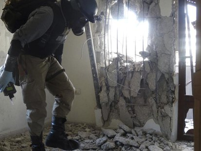 A U.N. chemical weapons expert, wearing a gas mask, inspects one of the sites of an alleged chemical weapons attack in the Damascus' suburb