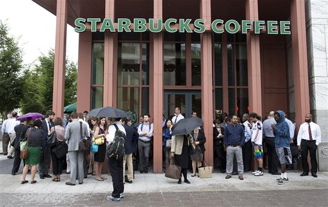 People stand outside a Starbucks Coffee shop that has been closed as police respond to a shooting at the Washington Navy Yard in Washington,