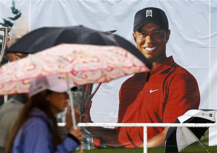 Golf fans walk past a poster of Tiger Woods during a rain delay at the BMW Championship golf tournament at the Conway Farms Golf Club in Lak