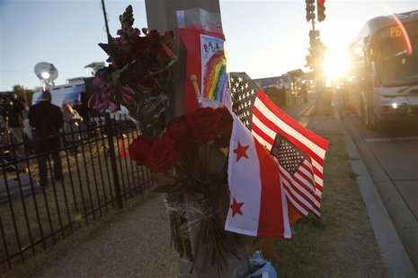 Flowers, flags and a child's drawing are pictured at a makeshift memorial outside the Navy Yard two days after a gunman killed 12 people bef