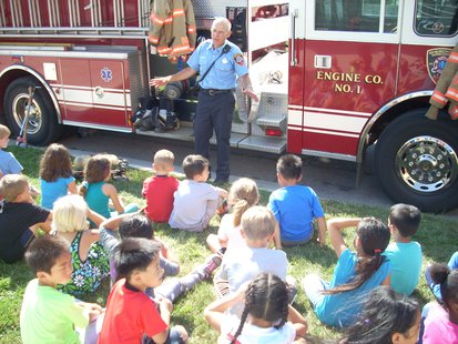 A group of 1st grade students at Jefferson Elementary School receiving a tour of a Sheboygan Fire Department truck.