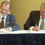 WMU President John Dunn and Cooley Law School President Don LeDuc sign the Affiliation Agreement.