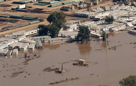An oil storage tank on a well pad lies toppled near portable buildings surrounded with flood waters in Weld County, Colorado September 17, 2
