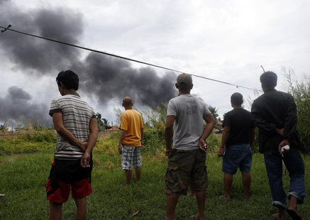 Villagers watch the smoke as fighting rages between government soldiers and the Muslim rebels of the Moro National Liberation Front (MNLF),