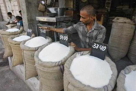 A vendor arranges a price tag over a sack filled with sugar at a wholesale vegetable market in the western Indian city of Ahmedabad Septembe
