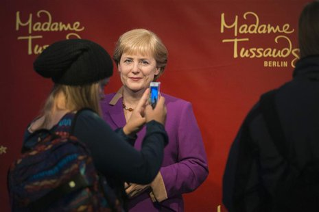 A tourist takes a picture of the wax figure of German Chancellor Angela Merkel at the Madame Tussauds wax museum in Berlin, September 19, 20