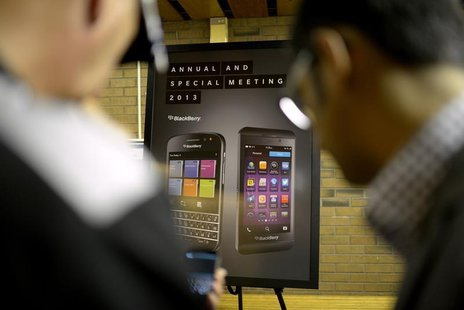 BlackeBerry users look at a new mobile device at the BlackBerry Annual and Special Meeting in Waterloo, Ontario July 9, 2013. REUTERS/Jon Bl