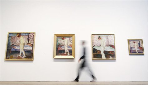 "Duncan Holden of the Tate poses with four paintings of Edvard Munch's ""Weeping Woman"" series at the Tate Modern in London's Southbank, June"