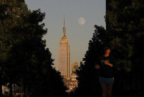 The moon rises at sunset behind New York's Empire State building as a woman runs along a promenade in Hoboken, New Jersey, September 17, 201