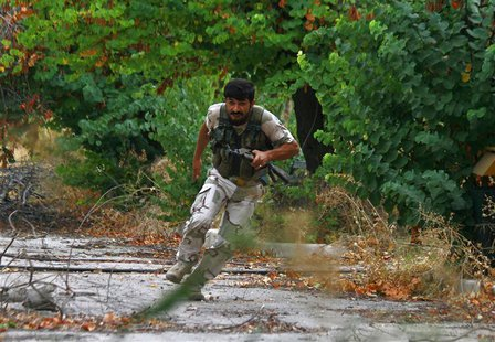 A Free Syrian Army fighter runs for cover from snipers loyal to Syria's President Bashar al-Assad in the Al-Sakhour neighborhood of Aleppo S