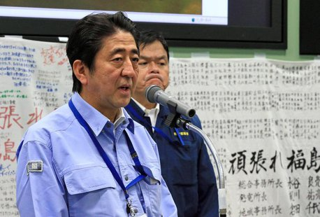 Japan's Prime Minister Shinzo Abe (L) speaks to workers at the emergency operation center during his inspection tour to Tokyo Electric Power
