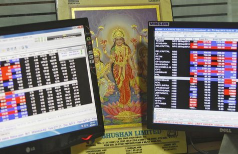 An image of Lakshmi, the Hindu goddess of wealth and prosperity, is placed between monitors displaying share price index at a share trading