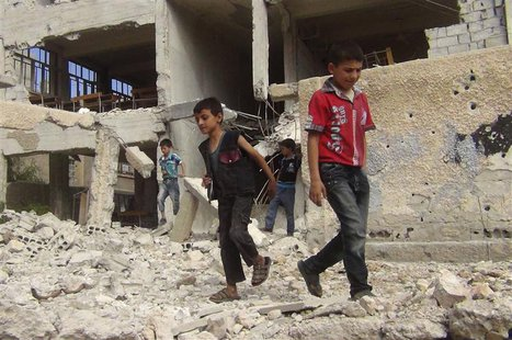 Children walk among debris from a damaged school building in the Damascus suburb of Zamalka September 19, 2013. Picture taken September 19,