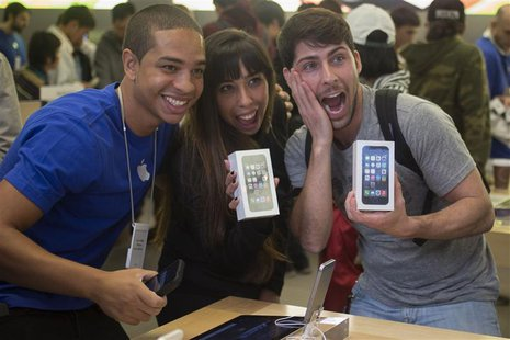 Alejandro de Rosa (R) and Melisa Racineti of Buenos Aires, Argentina pose with their new Apple iPhone 5s phones with Apple employee Jay at t