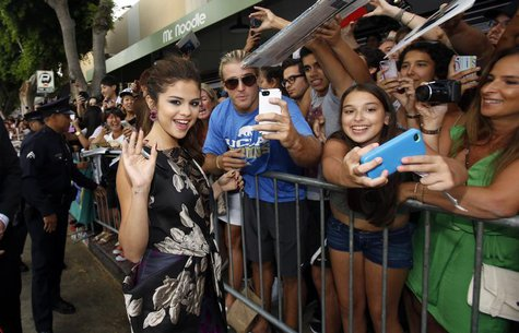 "Cast member Selena Gomez waves while greeting fans at the premiere of ""Getaway"" in Los Angeles, California August 26, 2013. REUTERS/Mario An"