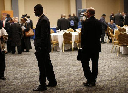 Job seekers stand in a room of prospective employers at a career fair in New York City, October 24, 2012. REUTERS/Mike Segar
