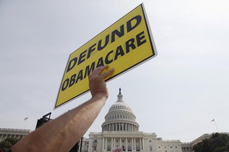 A man holds a sign at the Tea Party Patriots 'Exempt America from Obamacare' rally on the west lawn of the U.S. Capitol in Washington, Septe