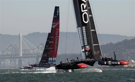 Emirates Team New Zealand (L) and Oracle Team USA sail after rounding the first mark during Race 12 of the 34th America's Cup yacht sailing