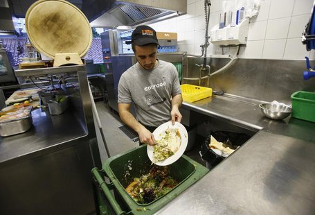 A cook throws away leftovers in the 'Auf da Muehle' restaurant in the western Austrian village of Soell June 2, 2013. REUTERS/Dominic Ebenbi