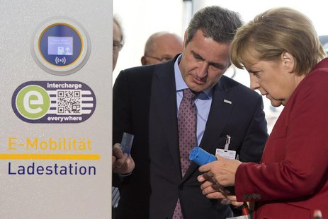 EnBW AG CEO Frank Mastiaux explains the operation of an electric car charging booth to German Chancellor Angela Merkel at the Electric Mobil