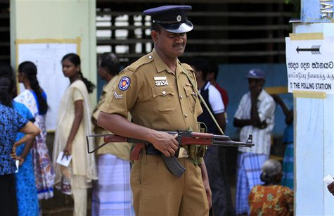 A police officer stands guard next to Tamil voters at a polling station during the first provincial polls in 25 years in Jaffna, a former wa
