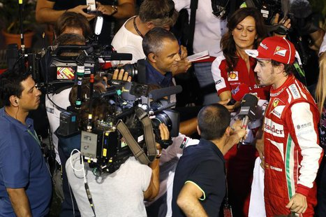 Ferrari Formula One driver Fernando Alonso of Spain is interviewed after the qualifying session of the Singapore F1 Grand Prix at the Marina