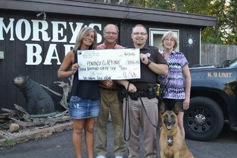 PHOTO - From left to right: Brenda Cote, owner of Morey's Bar, Mark Czech, Deputy Daniel Wachowiak, and Annette Glodowski – along with Baco.