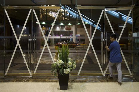 A man leaves a shopping mall, which entrances are taped in anticipation of Typhoon Usagi, in Hong Kong September 21, 2013. REUTERS/Tyrone Si