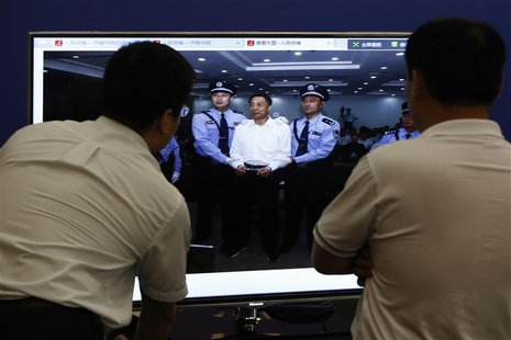 Men look at a screen displaying a picture of disgraced Chinese politician Bo Xilai standing trial on the website of a court's microblog, in