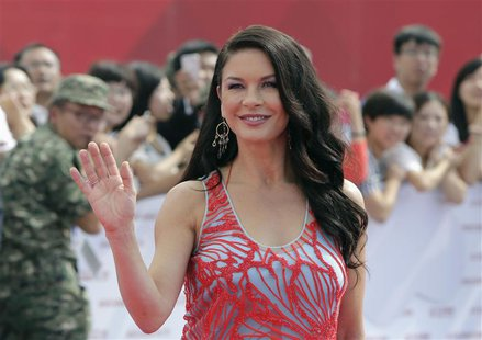 British actress Catherine Zeta-Jones waves to fans as she arrives for the launch ceremony of the Qingdao Oriental Movie Metropolis on the ou