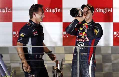 Red Bull team principal Christian Horner (L) stands on the podium with Red Bull Formula One driver Sebastian Vettel of Germany after Vettel