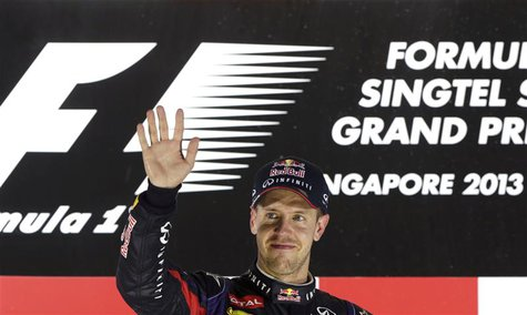 Red Bull Formula One driver Sebastian Vettel of Germany waves on the podium after the Singapore F1 Grand Prix at the Marina Bay street circu