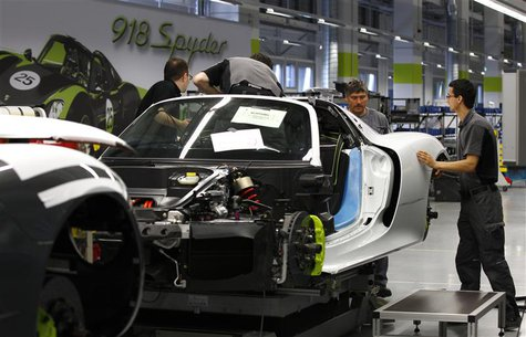 Workers assemble a new Porsche 918-Spyder sports car at the production line of the German car manufacturer's plant in Stuttgart-Zuffenhausen