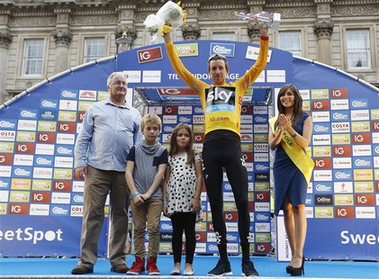 Britain's Bradley Wiggins (2nd R), with his children Ben and Isabella, celebrate being the overall winner of the Tour of Britain and receivi