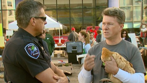 A man holds a chicken illegally at the Appleton Farm Market on Saturday, September 21, 2013. He and others protested the illegality of having livestock in public, but the legality of carrying firearms in public. (Photo by: FOX 11).
