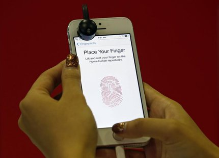 A promoter demonstrates the fingerprint scanner feature of the newly launched Apple iPhone 5S in Singapore September 20, 2013. REUTERS/Edgar