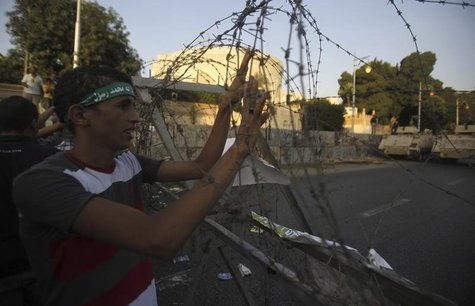 A member of the Muslim Brotherhood and supporter of ousted Egyptian President Mohamed Mursi holds onto barbed wire as he shouts slogans agai