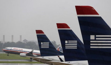 An American Airlines jet takes off while U.S. Airways jets are lined up at Reagan National Airport on the day U.S. Airways' stockholders are