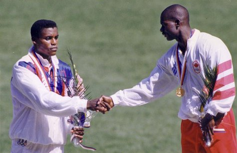 Ben Johnson of Canada (R), wearing his gold medal, shakes hands with silver medalist Carl Lewis of the U.S. after winning the men's 100 mete